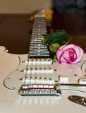 White guitar with a pink rose on the side of soundboard