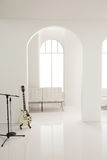 White guitar in white studio. A white guitar put in the white music studio royalty free stock images