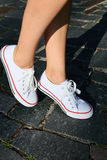 White gumshoes on woman legs. Hipster style Royalty Free Stock Images