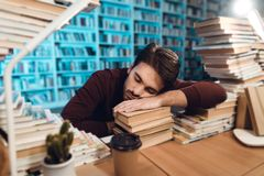 White guy surrounded by books in library. Student is sleeping. White guy sitting at table surrounded by books in library. Student is sleeping Stock Image