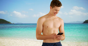 White guy wearing swim shorts using smart phone to read text messages on beach. Stock Photo