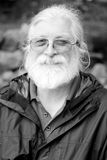 White Hair and Beard (BW). A black and white of an aged man with long white hair, glasses and a full beard. Shallow depth of field Royalty Free Stock Images