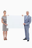 White hair businessman holding a big white sign. White hair businessman smiling and holding a big white sign with a women against white background Royalty Free Stock Photos
