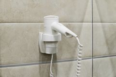 White Hair Dryer on wall in bathroom. SPA. royalty free stock images
