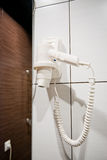 White Hair Dryer on wall in bathroom. Stock Photography