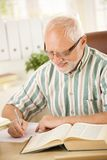 White hair pensioner writing letter at home. White hair pensioner sitting at desk, writing letter at home, smiling royalty free stock photo