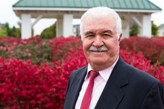 White Hair Senior Businessman Outside by the Red Burning Bushes Stock Photography