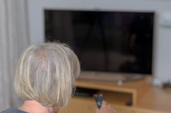 White Haired Adult Woman Holding TV Remote Control Royalty Free Stock Images