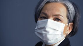 White-haired business woman in a protective mask looks at the camera standing on a dark background. Business concept