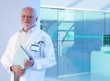 White haired doctor professor at hospital. Old white haired professor doctor standing in front of MRI room at hospital, holding tablet, smiling Royalty Free Stock Photo