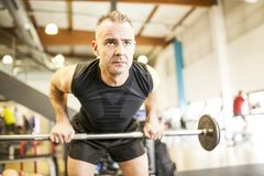 White-haired man lifting bar stock images