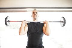 White-haired man lifting bar stock image