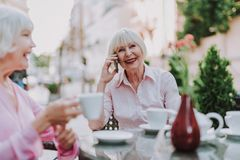 White-haired pretty lady speaking by the phone royalty free stock image