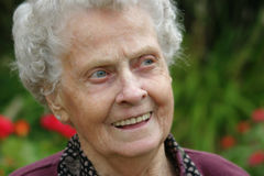 White Haired Senior. Elderly woman smiles as she gazes out into her garden Royalty Free Stock Photos