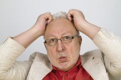 White haired senior with glasses tearing his hair Stock Images