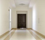 White hallway with marble floor and brown door Stock Image