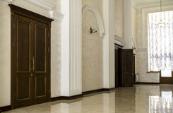 White hallway with marble floor, brown doors and window Royalty Free Stock Photography