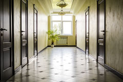 White hallway with marble floor, brown doors and window Stock Photo
