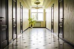 White hallway with marble floor, brown doors and window Stock Photo