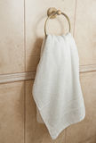 White hand towel on metallic hanger. Close up background of a bathroom hand towel on tile wall.  Stock Photos