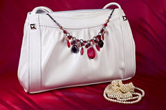 White handbag with necklace and pearls. Over red background Royalty Free Stock Photography