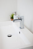 White handbasin with soap and a houseplant Royalty Free Stock Image