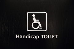 White Handicap Disabled Toilet Sign on Black Wood Stock Photo