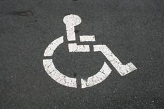 White Handicapped Symbol On Pavement. White Painted Handicapped Wheelchair Symbol On Pavement Stock Image
