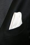 White Handkerchief. A white textured handkerchief is folded into the breast pocket of a tuxedo Stock Photos