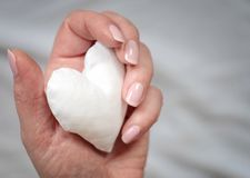 White handmade fabric heart in woman`s hand on grey background royalty free stock image