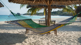 White handmade hammock with palm tree on Zanzibar beach. White handmade hammock with palm tree on clean Zanzibar beach and clear ocean on the background Royalty Free Stock Photography