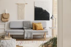 White handmade macrame above grey comfortable sofa with orange pillows and warm blanket, real photo with mockup on the empty wall royalty free stock images