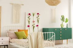 White handmade macrame above single metal bed with colorful pillows and doted bedding in fashionable boho bedroom interior with stock photo