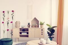 White handmade macrame above wooden cabinet with books, plants and vases in elegant boho interior with flower board. Concept stock photography