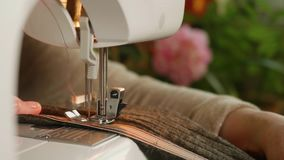 White hands cut fibre and sew on electrical sewing machine. Close up view. stock video footage