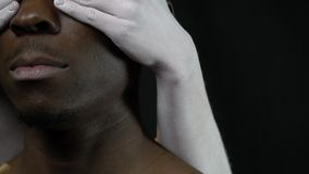 White hands of the girl close the eyes of black men. A black man with a beard, women`s hands in a white makeup close their eyes stock footage
