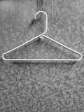 White Hanger on Coat Rack with Pattern Wall Royalty Free Stock Images