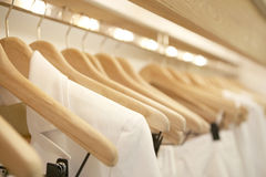 White on Hangers. Detail of white clothes hanging on wooden hangers in a fashion store Royalty Free Stock Photos