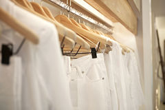 White on Hangers. Detail of white clothes hanging on wooden hangers in a fashion store Stock Photo
