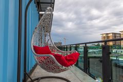 White hanging chair with red cushion. Located on the front porch. The sky and the clouds are the background. For a relaxing day stock images