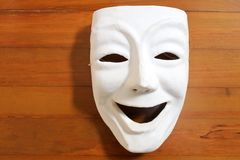 White happy human face expression mask with on a wooden table. Flat lay view of a white happy human face expression mask with on a wooden table. Happiness Royalty Free Stock Image