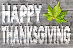 White Happy Thanksgiving written on wooden board background with one green leaf Royalty Free Stock Photos