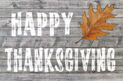 White Happy Thanksgiving written on wooden board background with one leaf Stock Image