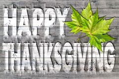White Happy Thanksgiving written on wooden board background with two green leaf Stock Photo