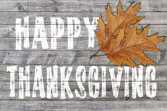 White Happy Thanksgiving written on wooden board background with two leaf Royalty Free Stock Photos