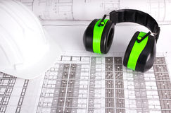 White hard hat and earmuffs blueprint Royalty Free Stock Image