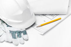 White hard hat on the gloves and pencil. On the druft, isolated on white background Stock Photo