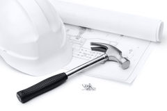 White hard hat, hammer, nails and druft Royalty Free Stock Image
