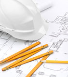White hard hat near working materials. White hard hat near working stuff: drawings, pencil, rule for building needs Royalty Free Stock Image