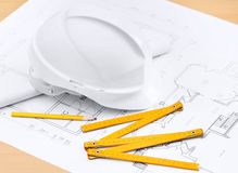 White hard hat near working tools. White hard hat near working drawings, pencil, rule for building needs Stock Photography